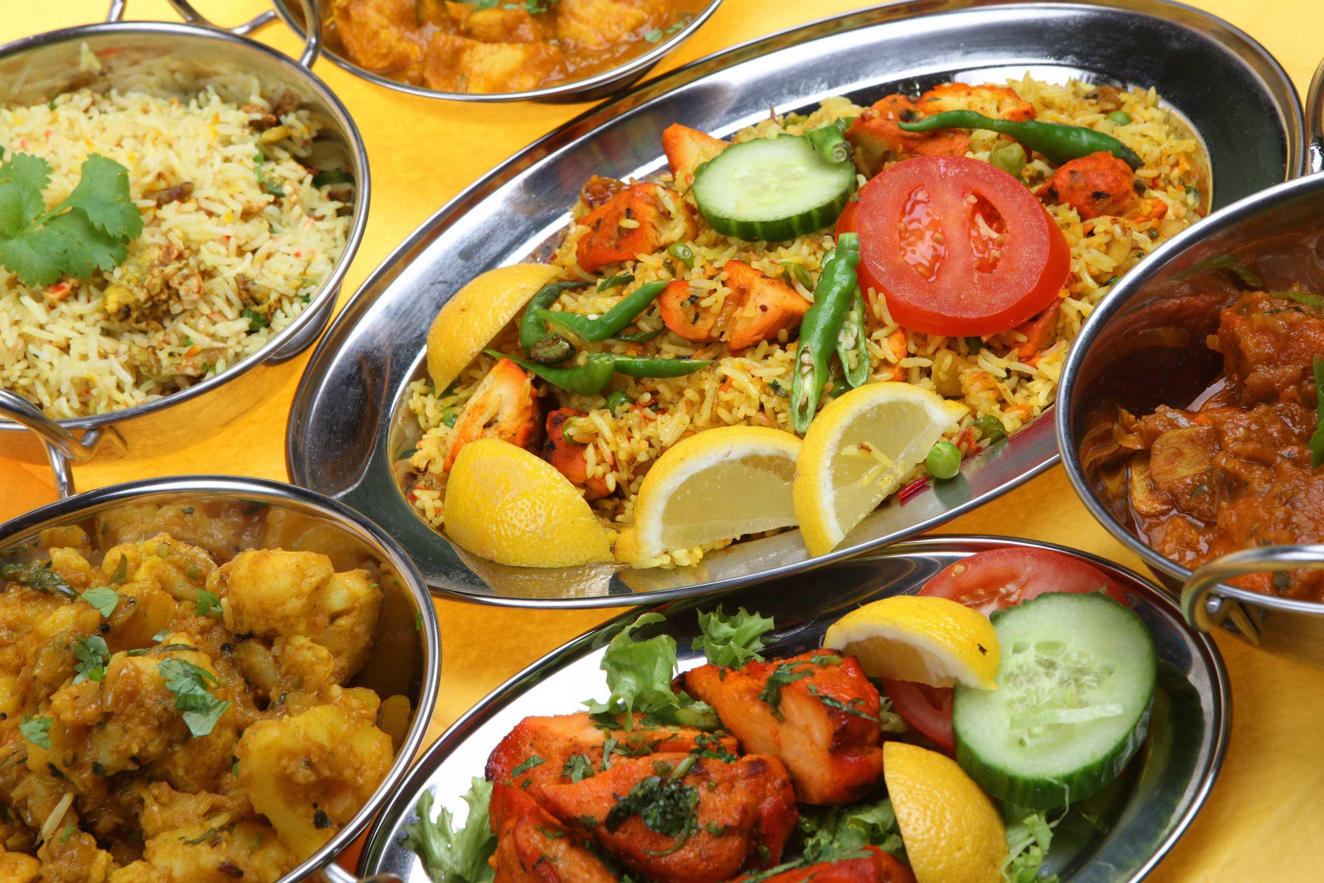 Bucataria indiana cu ingredientele sale tipice: orez, legume, curry si carne de pui.