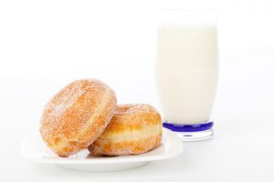 gogosi pufoase - doua gogosi pufoase langa un pahar cu lapte